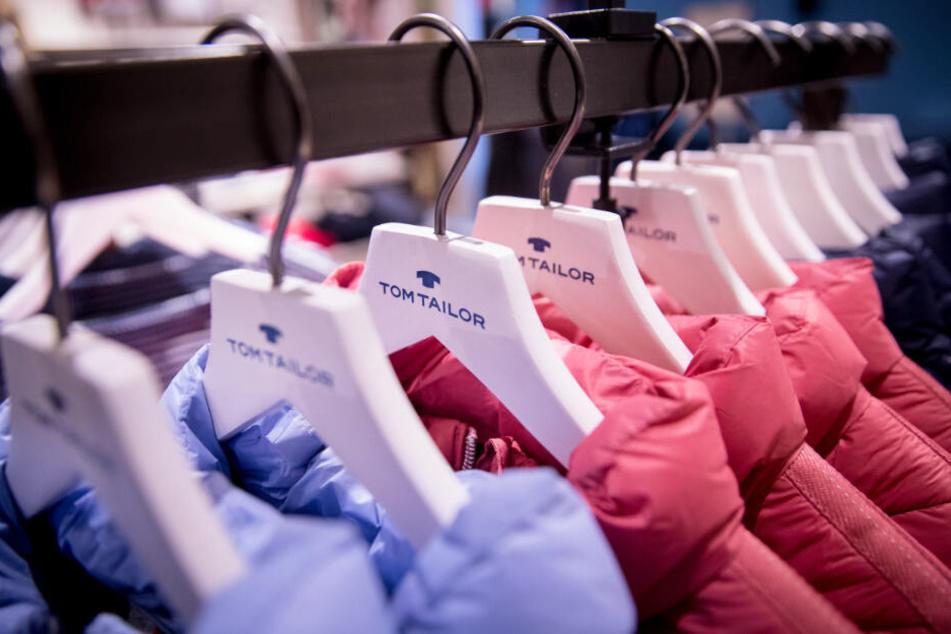 Jacken von Tom Tailor hängen auf einer Kleiderstange. (Archivbild)