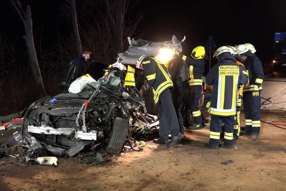 Die Feuerwehrleute untersuchen den Unfallwagen auf der B38.