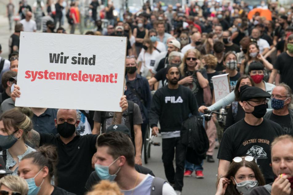 """""""Wir sind systemrelevant!"""" steht auf einem Plakat, das einer von rund hundert Menschen auf einer Demonstration der Veranstaltungsbranche zeigt."""