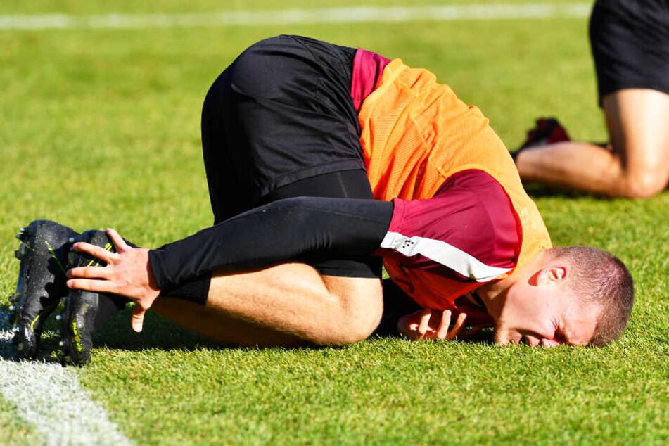 ...und mit schmerzverzerrtem Gesicht, sich den verletzten Knöchel haltend beim Training auf dem Rasen liegend.