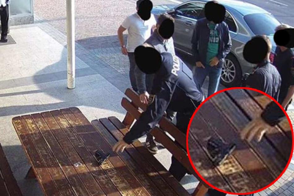 """Die Schusswaffe des falschen Polizisten wird von der """"echten"""" Polizei sichergestellt."""