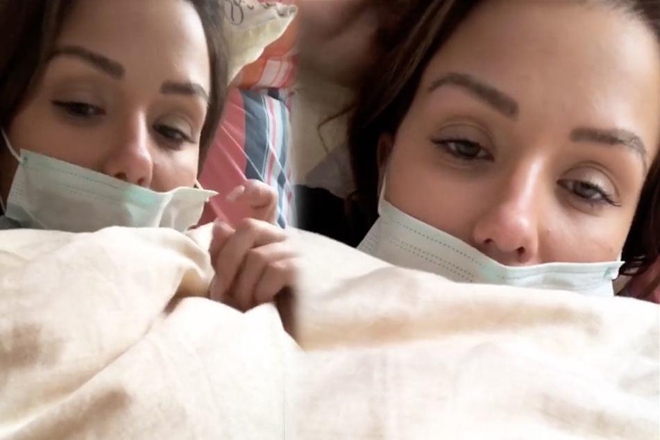 Kim Gloss mit Mundschutz im Bett. Die Sängerin leidet an Scharlach.
