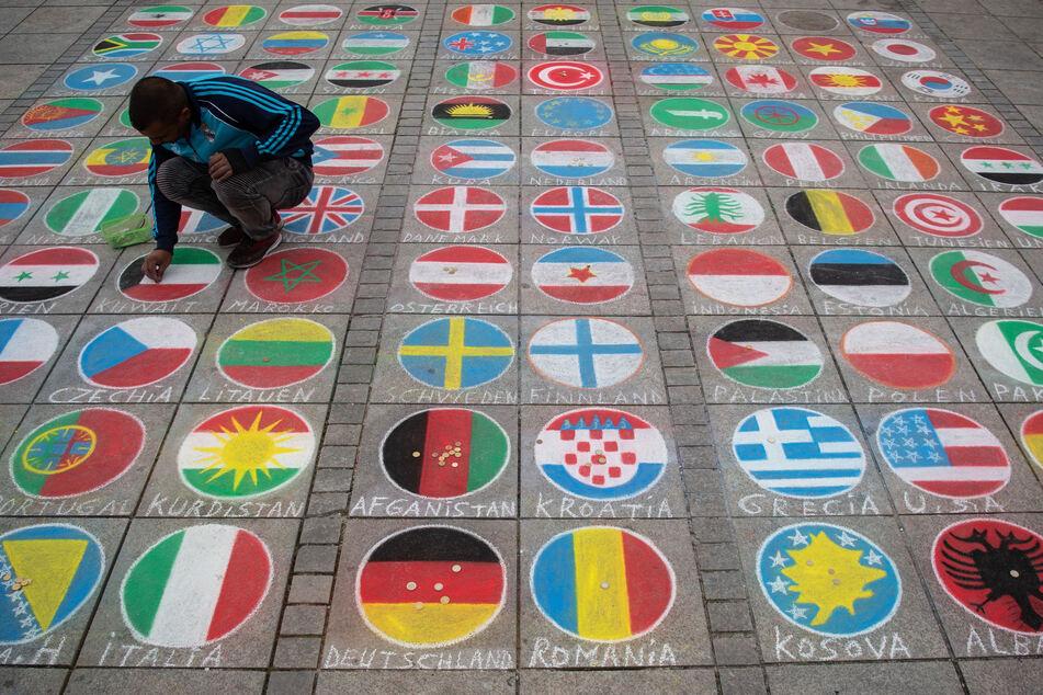 Kreidemalerei in Stuttgart: Ein Künstler malt internationale Flaggen auf die Straße (Foto: Marijan Murat/dpa)