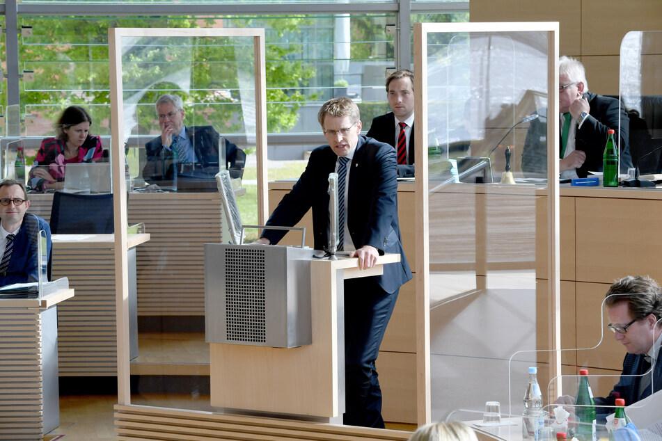 Daniel Günther (CDU, M), Ministerpräsident von Schleswig-Holstein steht an dem durch Plexiglasscheiben geschützten Rednerpult im Landtag.