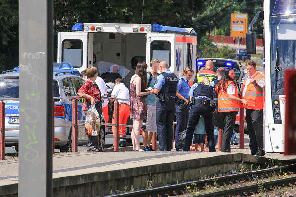 Polizisten nehmen Zeugenaussagen auf, während die Frau in einen Rettungswagen geschoben wird.