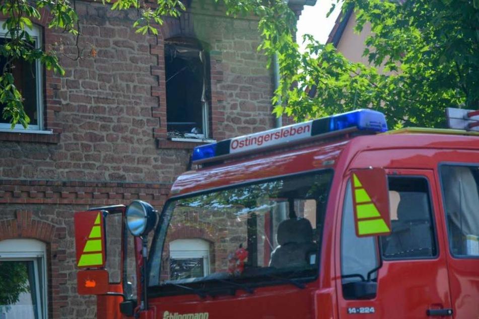 Rettungskräfte vor dem Haus in Erxleben bei Magdeburg. Über dem Fenster sind deutliche Rußspuren zu erkennen.