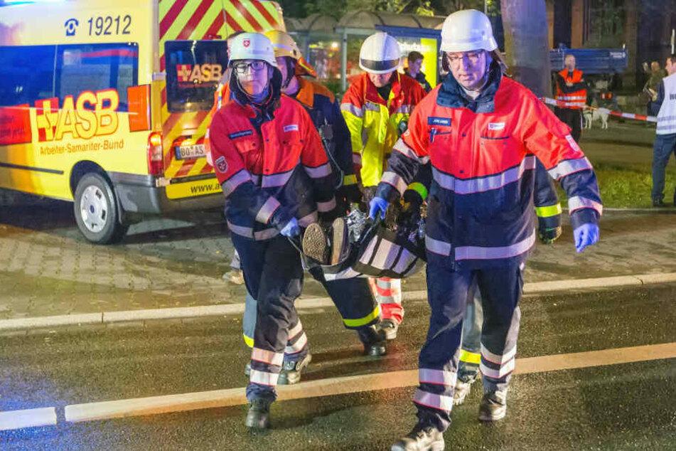 Katastrophenschützer der Malteser tragen einen Verletzten fort - bei Blaulicht-Einsätzen arbeiten ehrenamtliche und professionelle Retter Hand in Hand.