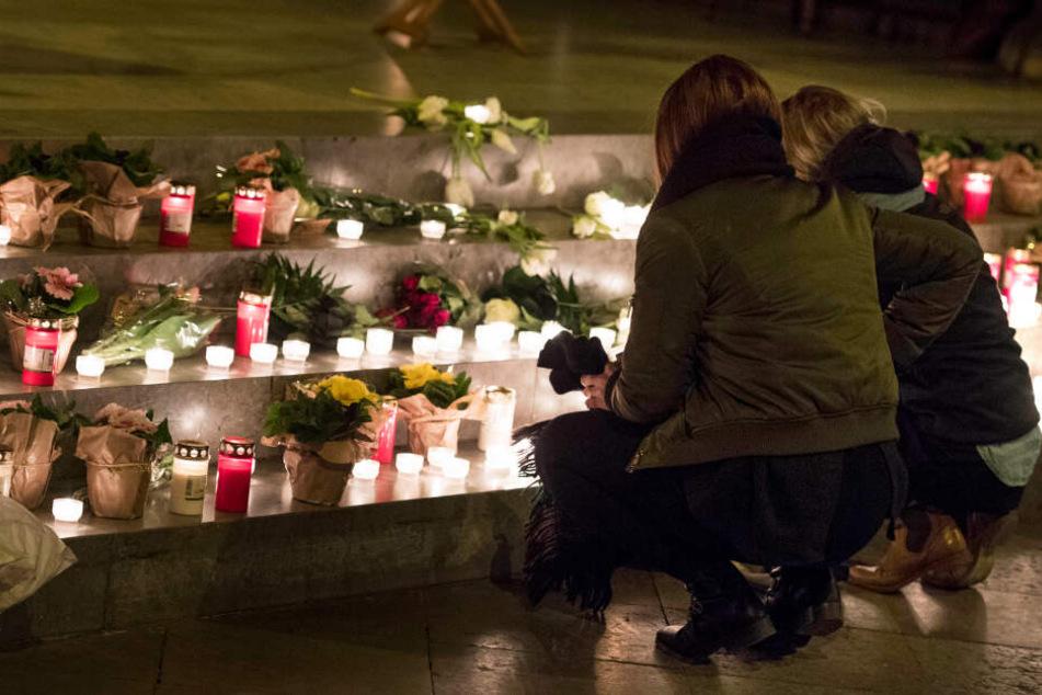 Zwei junge Frauen legen Blumen und Kerzen bei der Gedenkfeier für die getötete Mireille ab.