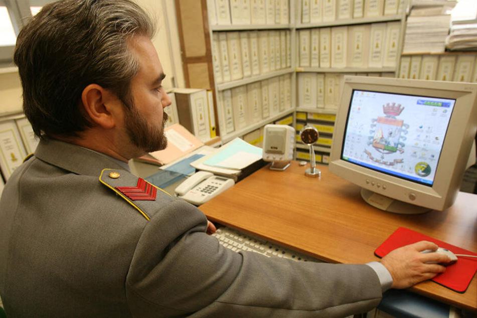 Ein Polizist der italienischen Guardia di Finanza (Finanzpolizei) sitzt vor einem Computer und prüft Steuererklärungen.