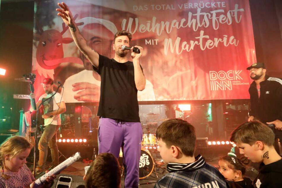 Marteria steht bei dem Weihnachtsfest mit Kindern und Jugendlichen in Rostock auf der Bühne.