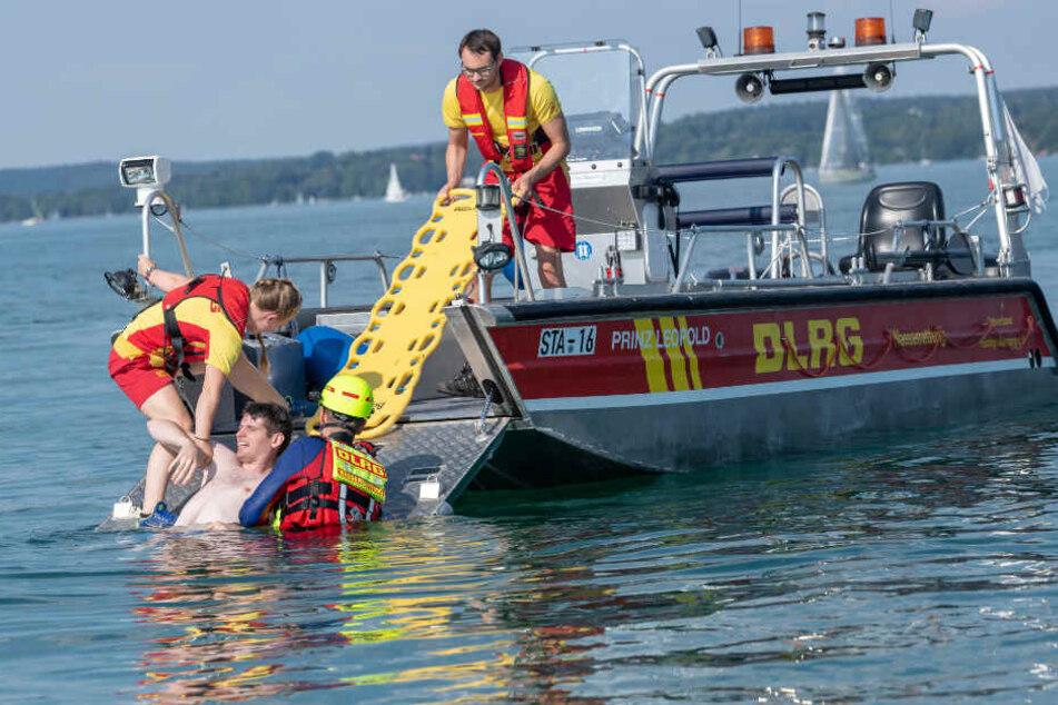 """Rettungsschwimmer ziehen bei einer Übung einen """"ertrinkenden"""" Mann aus dem Wasser."""