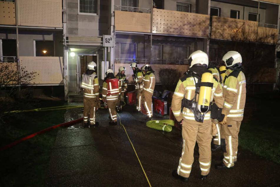 Feuerwehrleute stehen vor einem Wohnhaus Am Leutewitzer Ring.