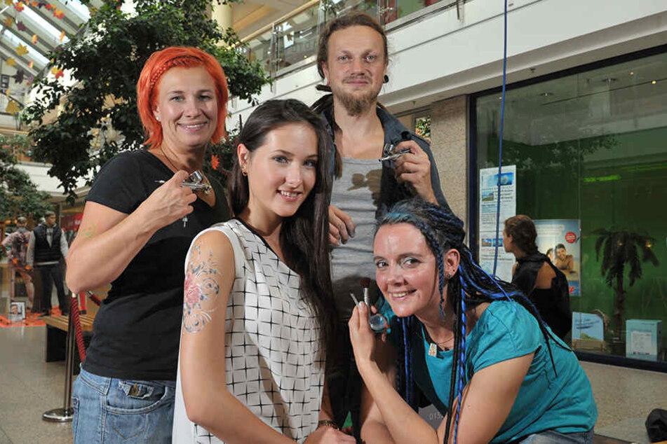 """Sabine Reichert (43), Sebastian Schindler (39) und Birgit Koniczek (33) von  """"Colorjunkies"""" verpassten auch MOPO24-Reporterin Isabel Möller (19) ein  Airbrush-Tattoo."""
