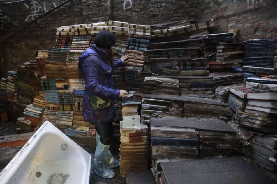 """Eine junge Frau überprüft den Zustand von Büchern aus der renommierten Buchhandlung """"Acqua Alta"""" (Hochwasser)."""