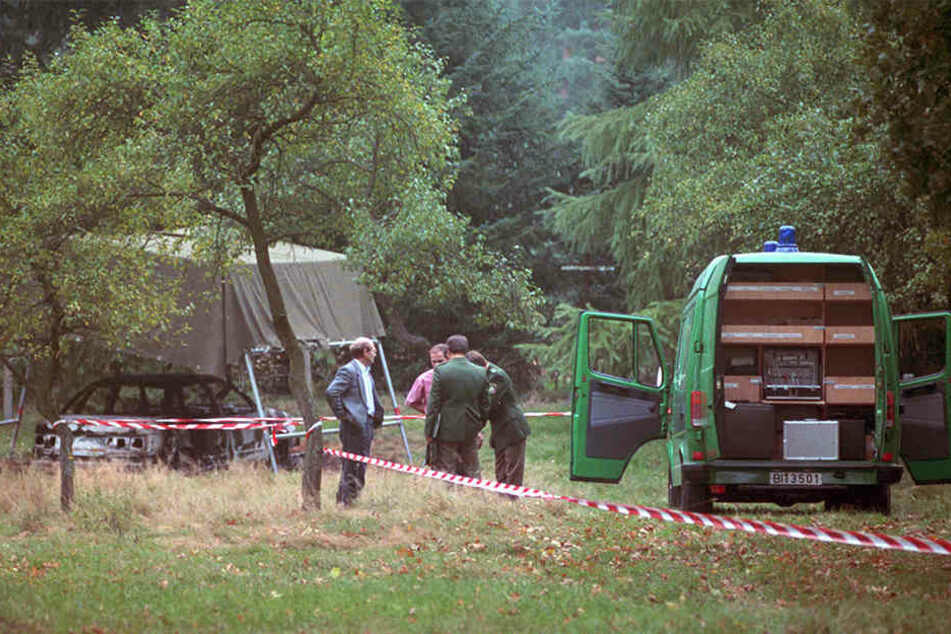 Polizeibeamte bei der Spurensuche auf einem Waldparkplatz.