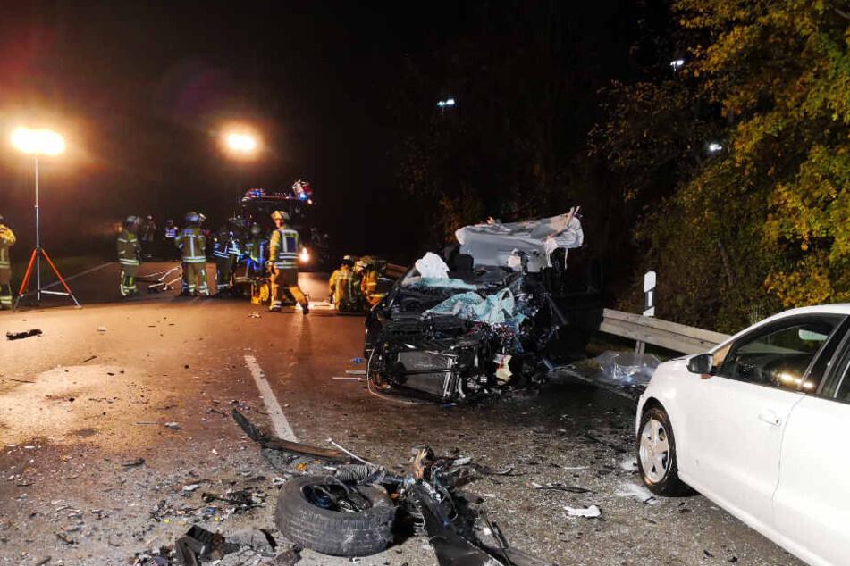 Trümmerteile liegen vor dem völlig zerstörten Auto.