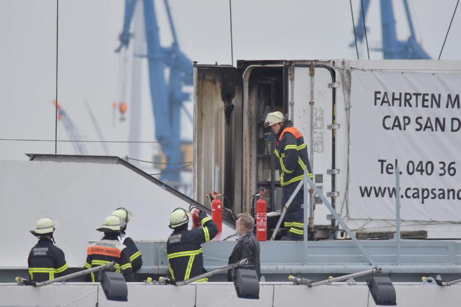 Feuerwehrleute begutachten den Container, in dem es brannte.
