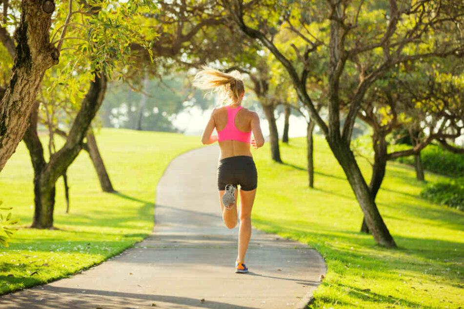 Eine Joggerin läuft durch einen Park. (Symbolbild)