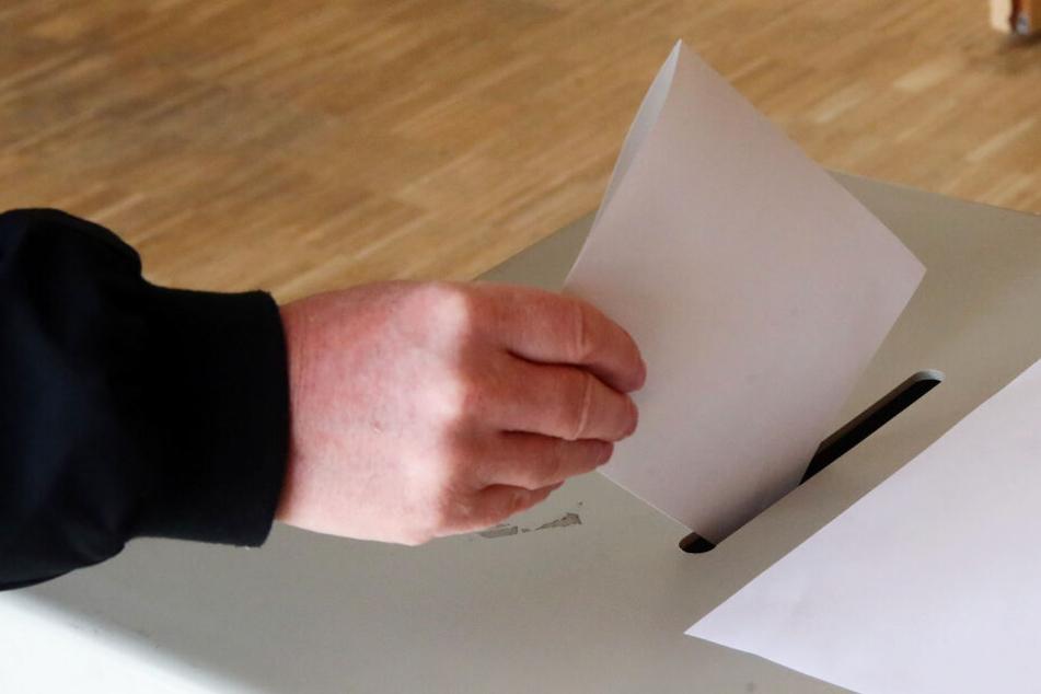 Eine Wählerin wirft ihren Wahlschein in eine Urne ein (Symbolbild)