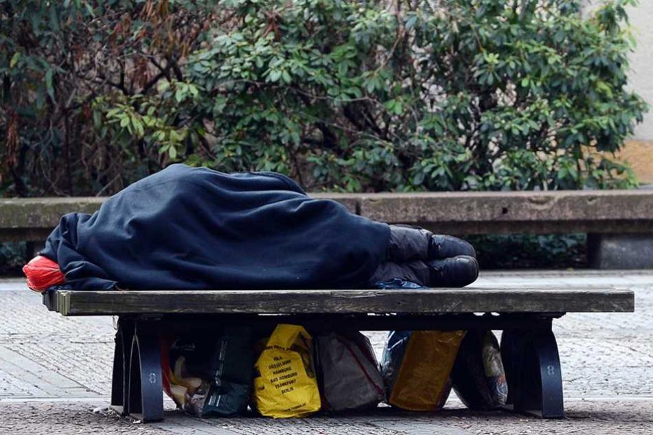 Ein Obdachloser liegt am Gendarmenmarkt auf einer Bank, unter der er seine Habseligkeiten in Tüten platziert hat.