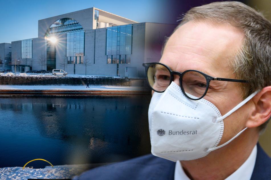 """Michael Müller (SPD), Regierender Bürgermeister von Berlin, sitzt mit einer Maske mit der Aufschrift """"Bundesrat"""" zu Beginn der 1000. Sitzung im Deutschen Bundesrat. Im Hintergrund ist das Bundeskanzleramt zu sehen. (Bildmontage)"""