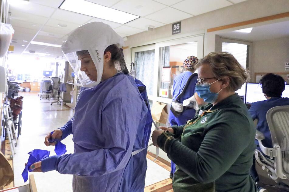 Deb Dalsing (r), Stationsleiterin einer Klinik in Madison, hilft der Krankenpflegerin Ainsley Billesbach beim Anziehen der Schutzkleidung. Bis vor kurzem hatte das Universitätsklinikum UW Health vier Flügel für Corona-Patienten. Um der wachsenden Nachfrage gerecht zu werden, wurde ein weiterer hinzugefügt.