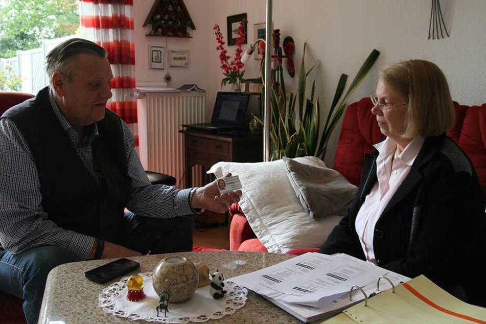 Friedhelm Tegeler vom Weissen Ring Minden-Lübbecke übergibt Ingrid Liebs ihren Mitarbeiterausweis.