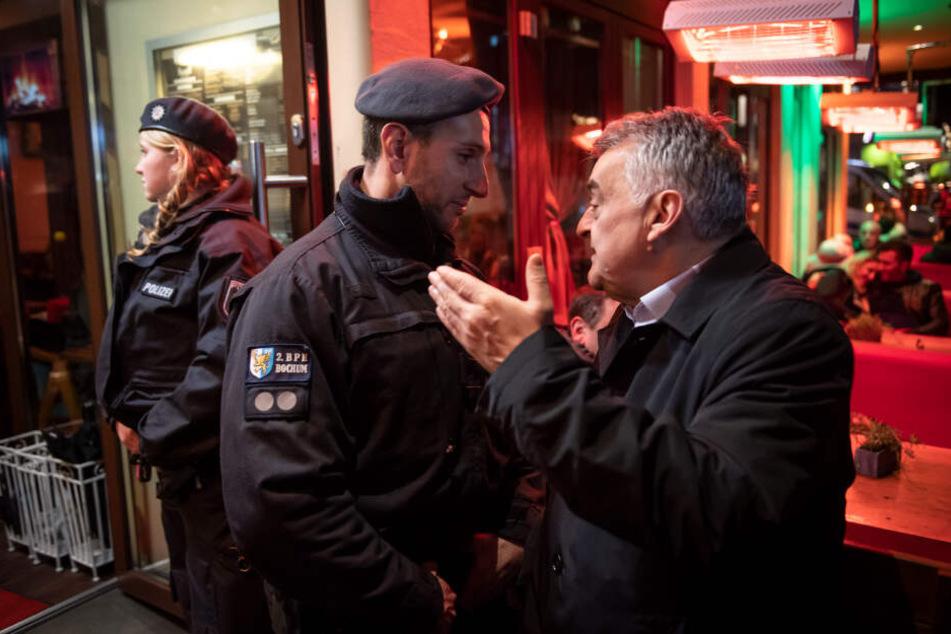 Innenminister Herbert Reul unterhält sich während der Razzia von Zoll und Polizei in einer Shisha-Bar mit einem Polizisten.