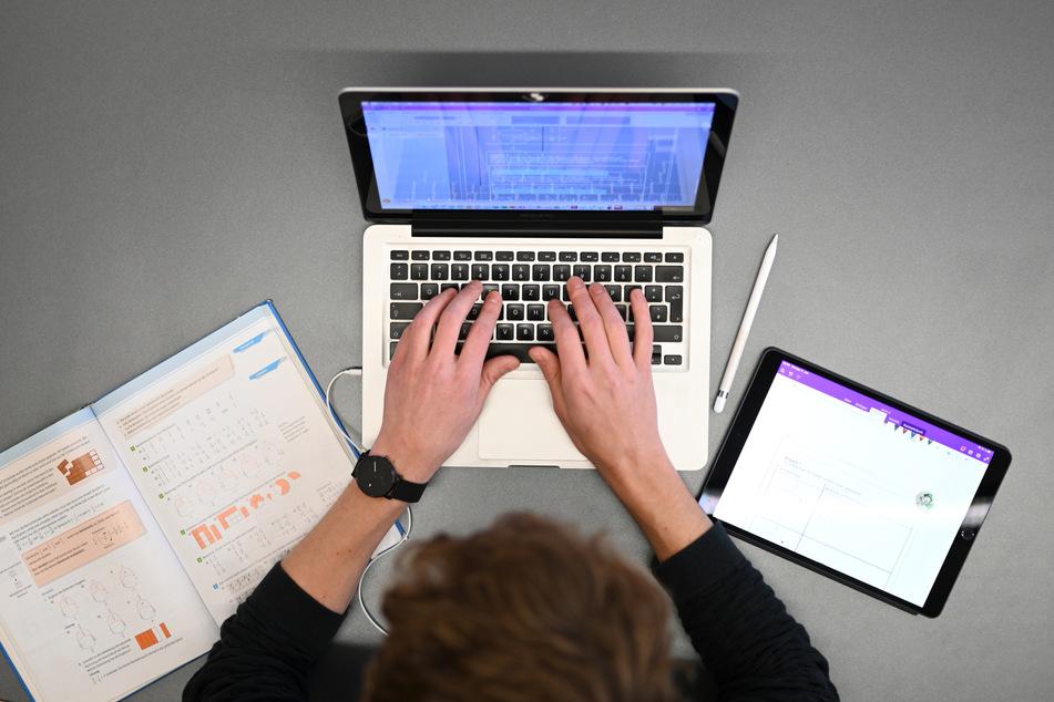 Ein Lehrer für Mathematik und Spanisch unterrichtet im Lehrerzimmer am Laptop.