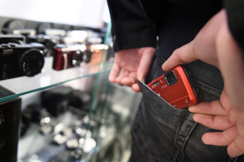 Ein Mann schiebt in einem Fotogeschäft in Ravensburg eine Kompaktkamera in seine Hosentasche. (Symbolbild)