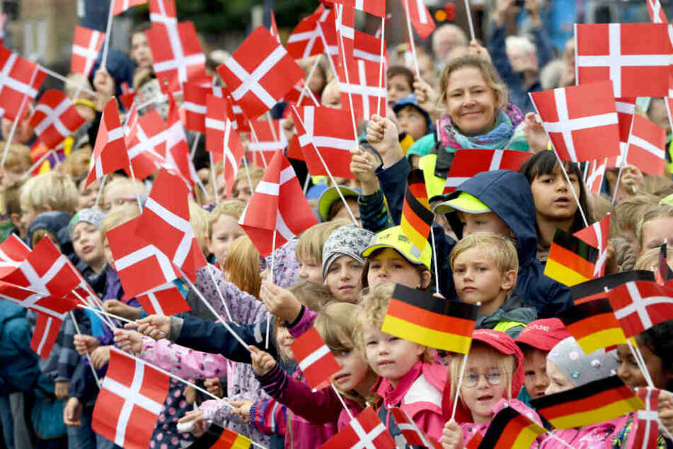 Kinder einer dänischen Schule begrüßen die Königin mit dänische Fähnchen.
