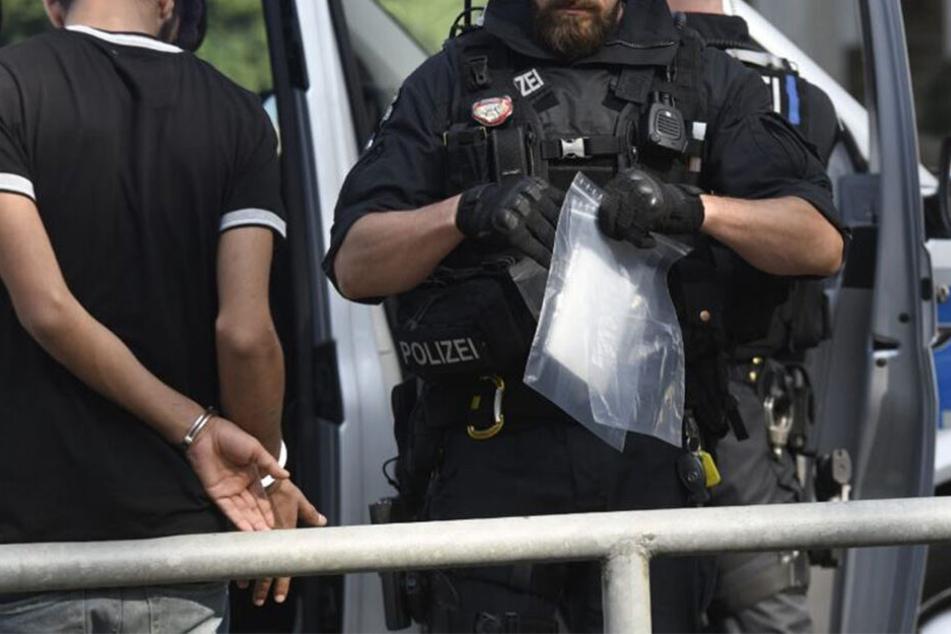 """Ein Polizist hält einen Teil der beschlagnahmten """"Ware"""" in der Hand."""