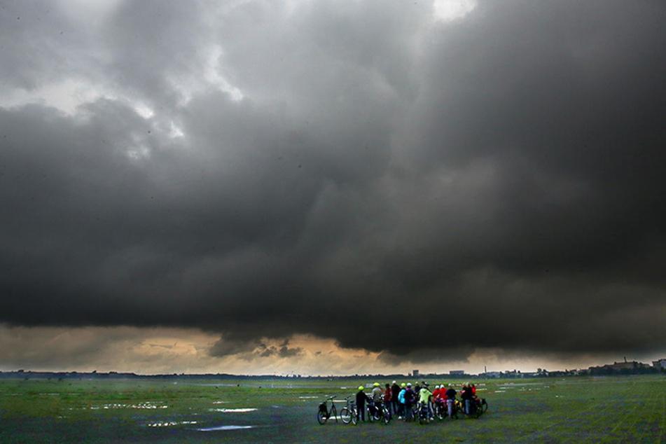 Eine Gruppe Radfahrer steht auf dem Gelände des ehemaligen Flughafens Tempelhof in Berlin, während sich über ihnen dunkle Regenwolken zusammen brauen.