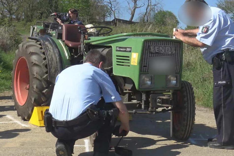 Polizisten untersuchen den Traktor, der den 82-Jährigen schwer verletzte.