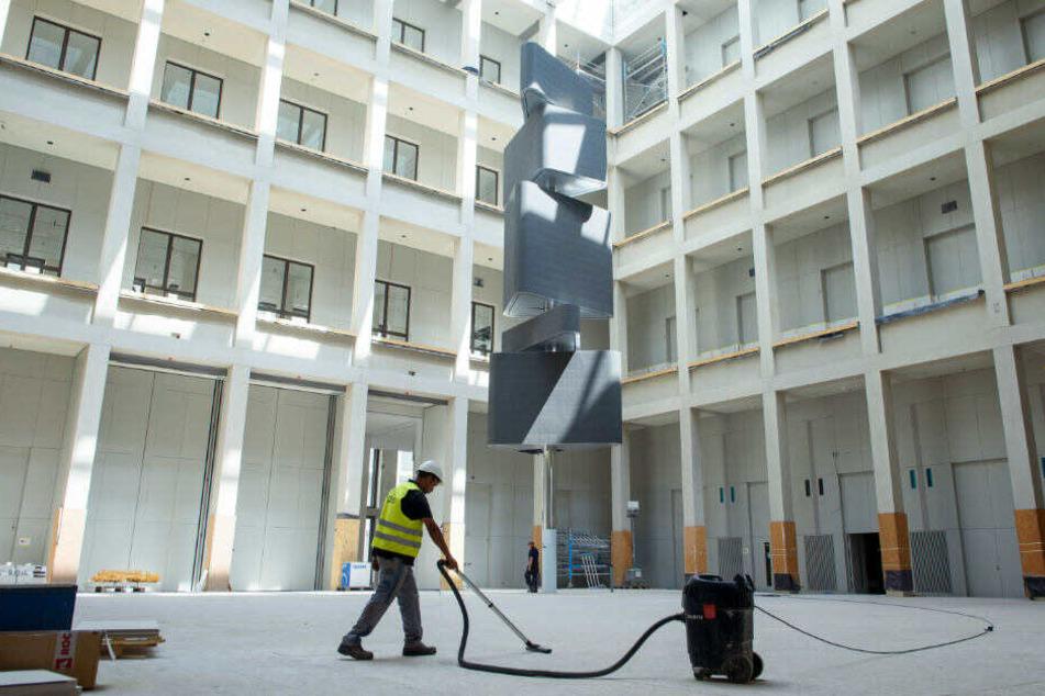 Ein Arbeiter saugt den noch abgedeckten Boden des Humboldt-Forums im neuen Berliner Stadtschloss.