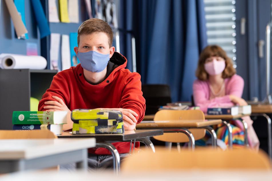 Schüler und Schülerinnen nehmen am Unterricht teil und tragen Mundschutze.