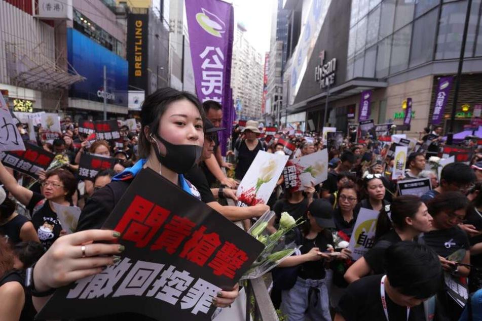 Demonstranten versammlen sich mit Plakaten für einen Protest gegen das Auslieferungsgesetz.