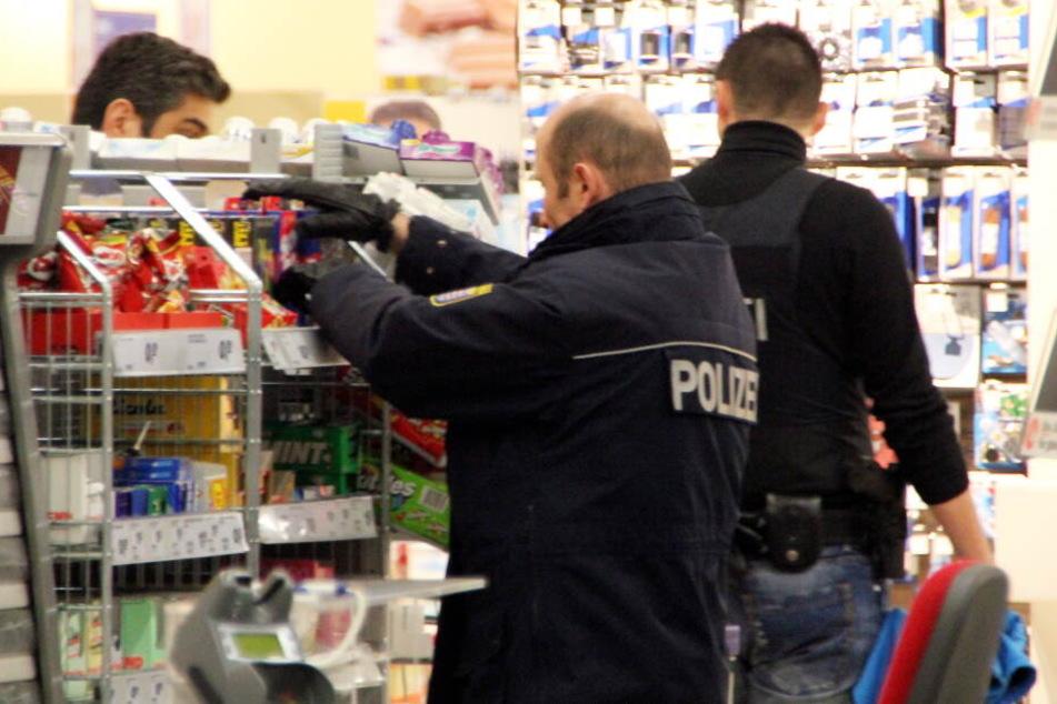 Polizisten durchsuchen einen Drogeriemarkt. (Symbolbild)