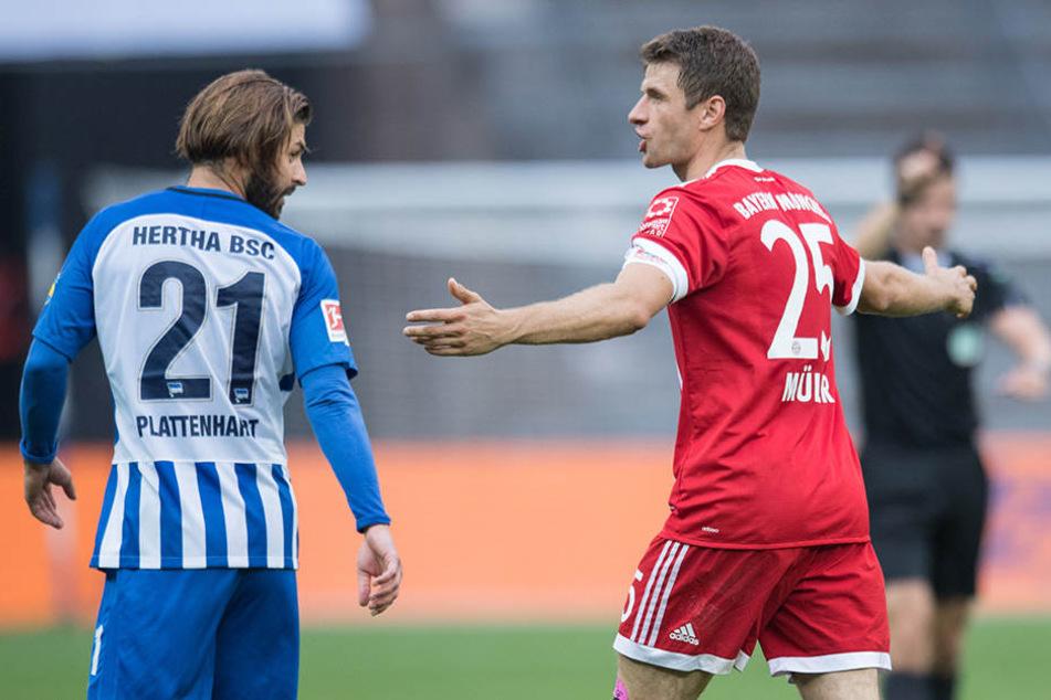 Bayerns Thomas Müller (r) steht mit einer ratlosen Geste auf dem Spielfeld und blickt zu Berlins Marvin Plattenhardt.