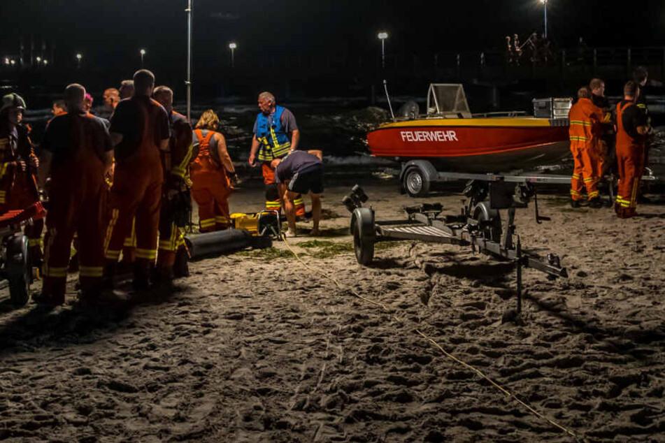 Rettungskräfte beraten sich am Sonntagabend am Strand von Scharbeutz.