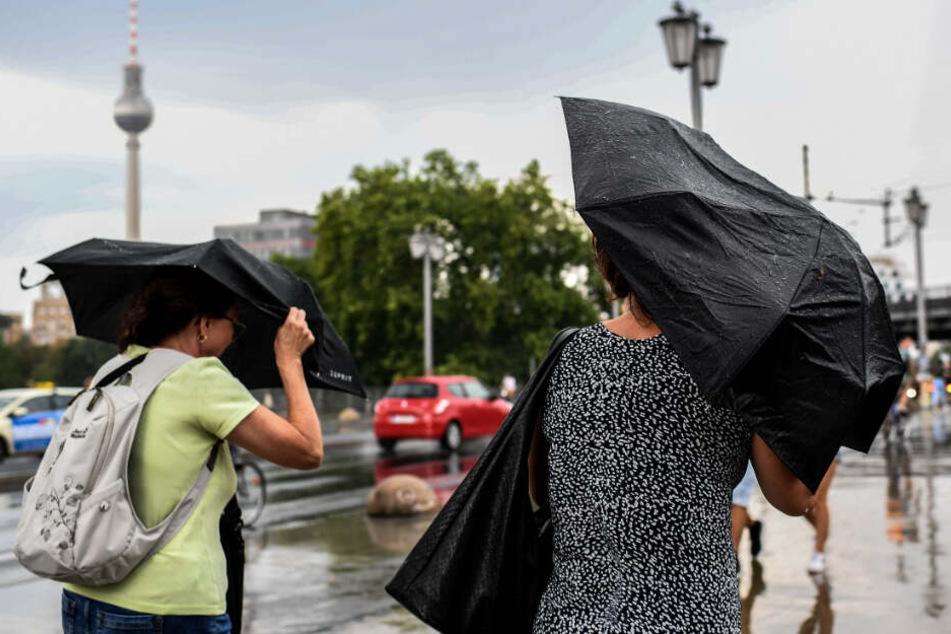 Zwei Frauen versuchen sich vor dem Regen mit Schirmen zu schützen.
