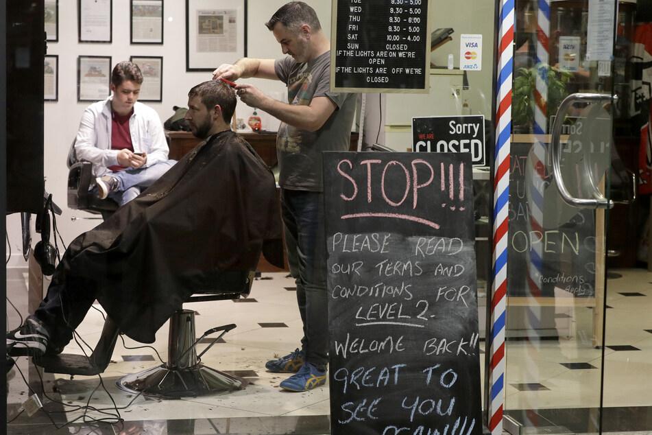 Conrad Fitz-Gerald, Besitzer des Friseursalons Cathedral Junction Barbers, schneidet einem Kunden kurz nach Mitternacht die Haare. In Neuseeland wurden die coronabedingten Ausgangssperren in der Nacht zum 14.05.2020 weiter gelockert. Jetzt können die meisten Geschäfte und öffentlichen Plätze wieder öffnen.