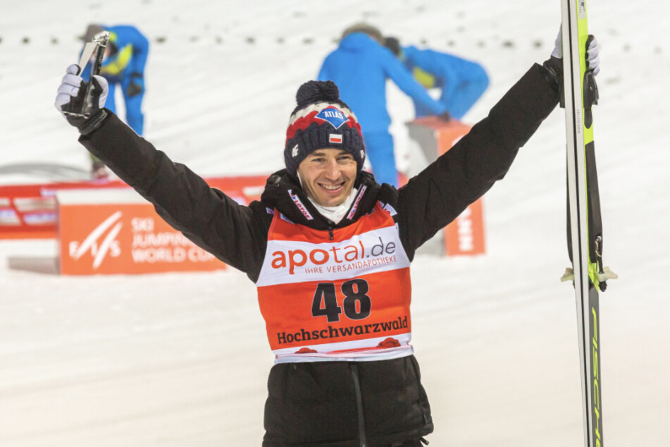 Der Pole Kamil Stoch jubelt nach der Siegerehrung und hält seinen Pokal in der Hand.