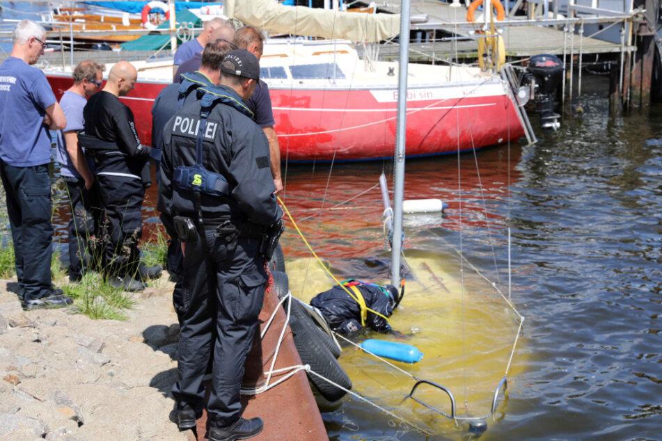 Boot sinkt in Hafen: Taucher suchen nach eingeschlossenen Menschen