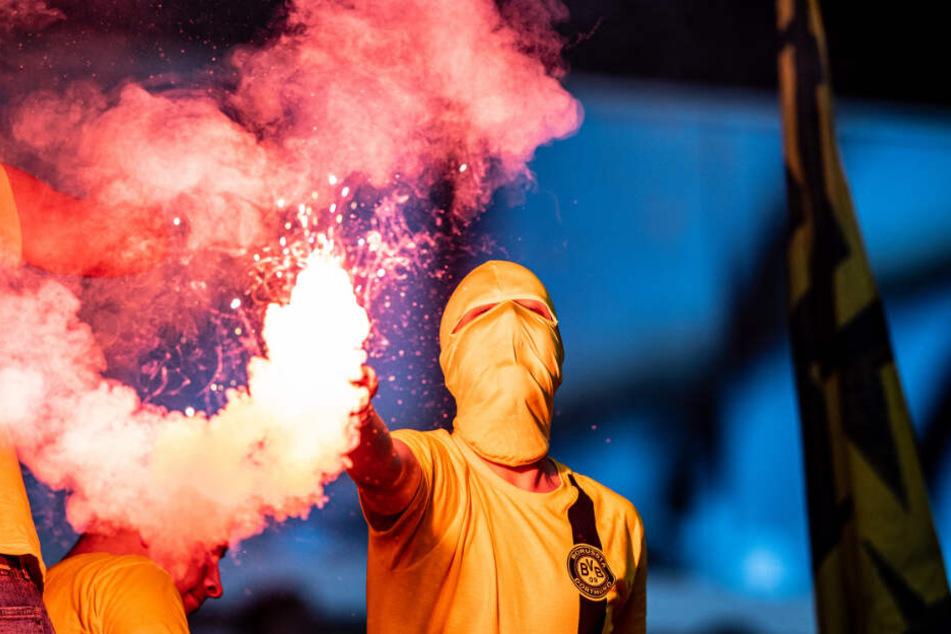 Ein vermummter BVB-Anhänger, der beim Revierderby am 9. Spieltag ein bengalisches Feuer abgebrannt hat.