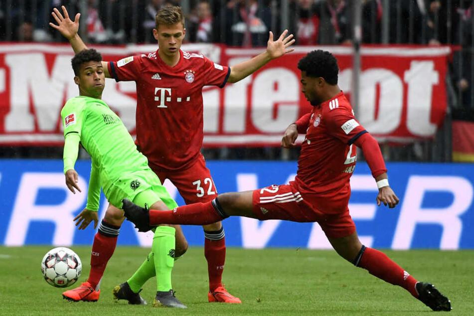Münchens Joshua Kimmich (M) und Serge Gnabry (r) kämpfen mit Linton Maina um den Ball.
