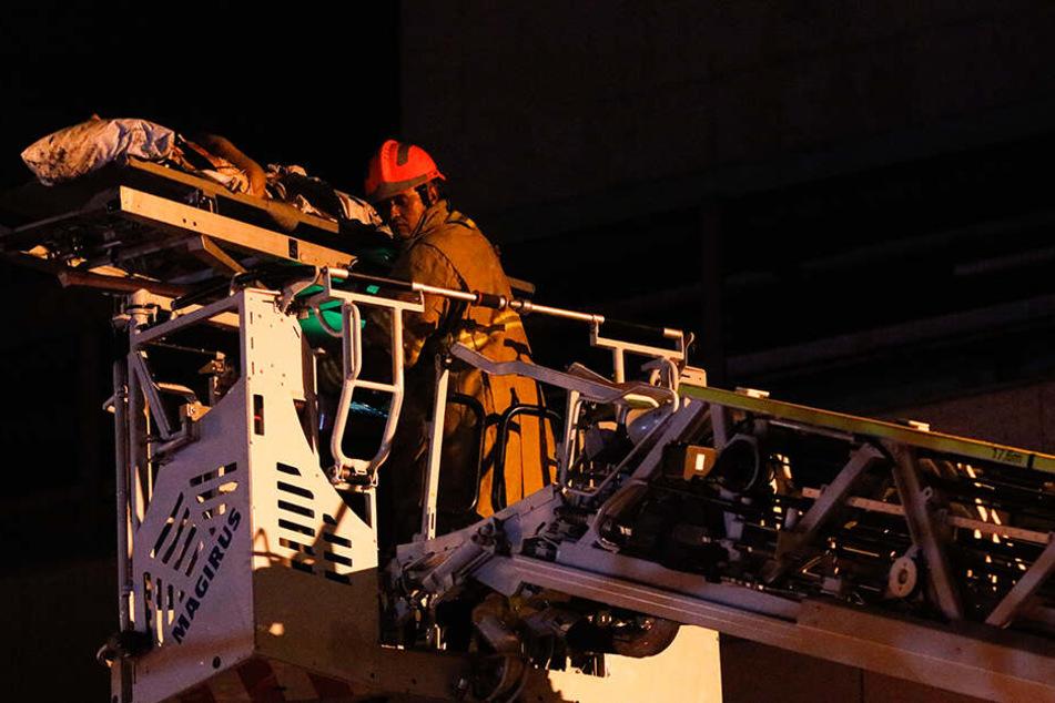 Ein Feuerwehrmann rettet eine Person mit einem Kran aus der Flammenhölle.