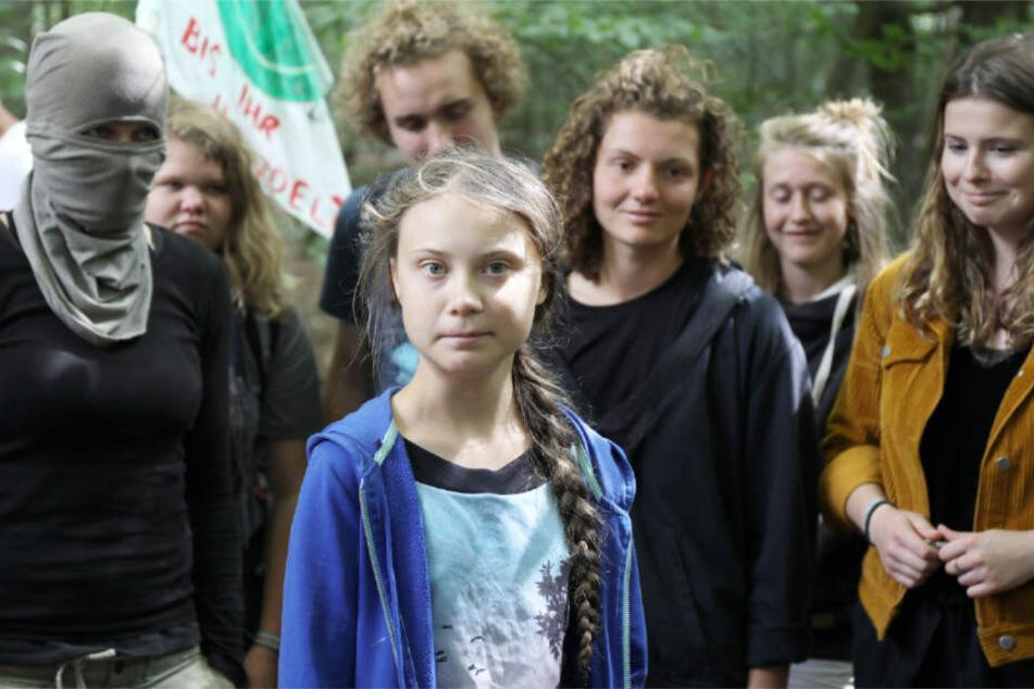 Greta Thunberg (Mitte), links von ihr eine vermummte Aktivistin im Hambacher Forst.