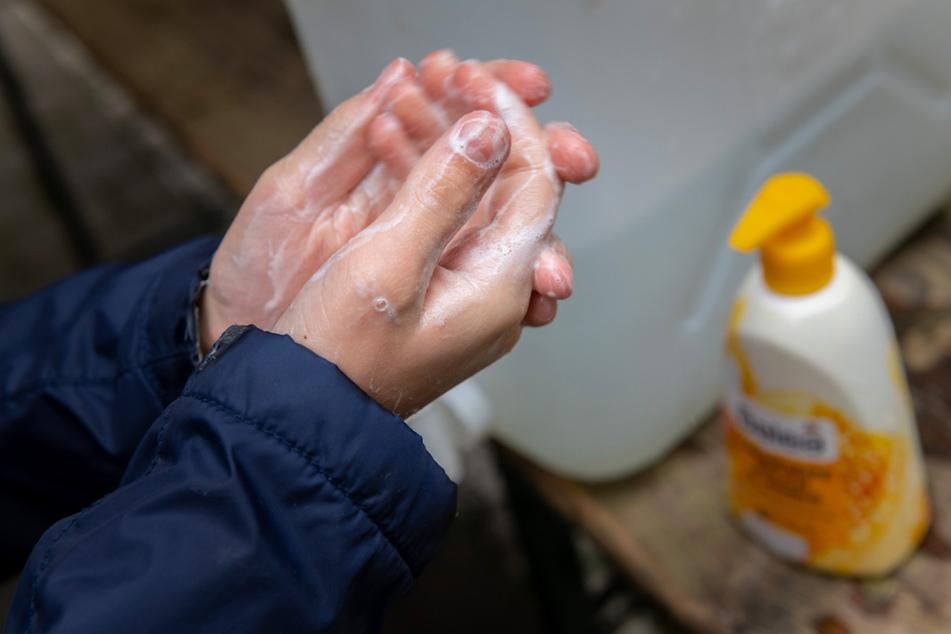 Ein Schüler wäscht sich am Morgen im Schulhof gründlich die Hände.