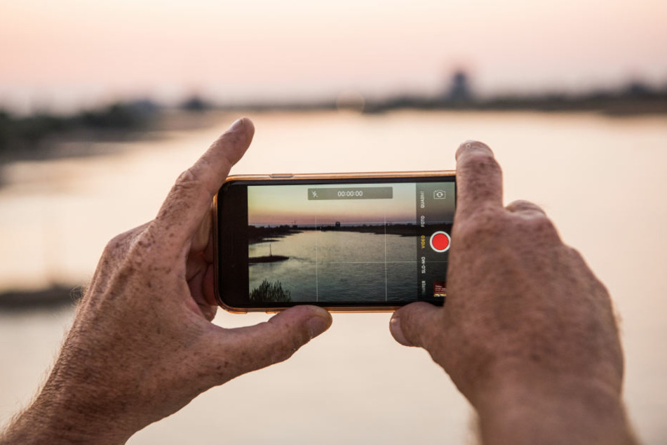 Mit einem Handy filmte der Unbekannte das kleine Mädchen beim Spielen in einem kleinen Fluss. (Symbolbild)